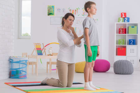Female physiotherapist checking back of young boy in shorts at school Stock Photo