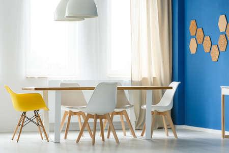 Interno scandinavo casa multifunzionale con tavolo comune, sedie bianche e gialle, muro blu, lampade e finestra con barriere ottiche Archivio Fotografico - 83769022