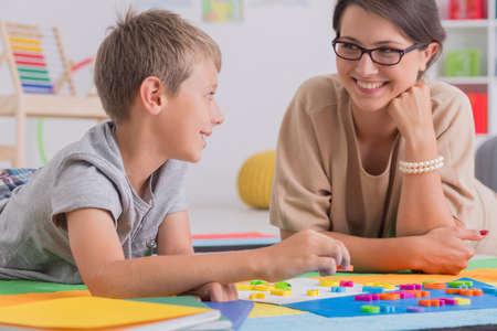 Blonde boy lying on floor with smiling elegant woman in colorful classroom Imagens