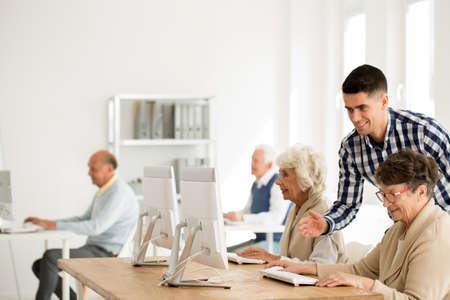 노인 여성 컴퓨터 문제 돕는 젊은 교사 스톡 콘텐츠