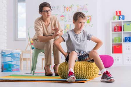 Beledigd kind dat vrouwelijke therapeut in ruimte met speelgoed de rug toekeert