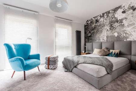 Monochromatische grijze slaapkamer met grungemuur, houten nachtkastje, witte muren en blauwe vintage stijlleunstoel Stockfoto