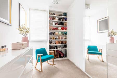 Dreamy feminine wardrobe with white furniture, big mirror, shoe closet, beige carpet, blue retro armchair and pastel pink accessories Standard-Bild