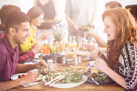 Handsome man enjoys tasty vegetarian meal with her red haired girlfriend in restaurant Stock Photo