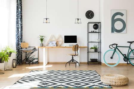 Dreieckregale auf einem einfachen, hölzernen Schreibtisch und Blumenplakat versteckt in der Ecke, hinter einem Stuhl Standard-Bild - 83779575