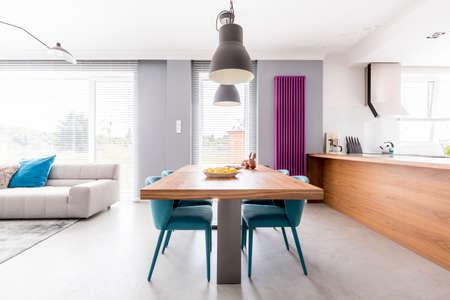 Offen geschnittenes Familienwohnzimmer mit Küchenzeile aus Holz, violettem Heizkörper, Gemeinschaftstisch mit türkisen Stühlen und geräumigem Wohnzimmer mit beiger Couch Standard-Bild - 83779583