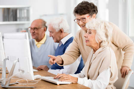 Elder lady with glasses helping her friend with computer issue
