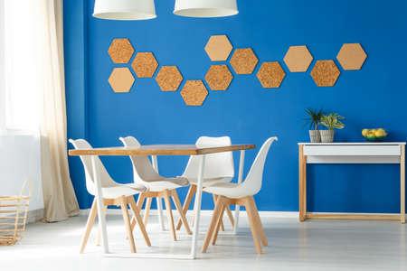 흰색과 나무 테이블, 의자 및 에코 코르크 벽 액세서리와 함께 파란 가족 식사 공간 디자인 아이디어