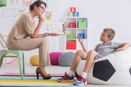 Young boy and elegant psychotherapist discussing a drawing in room with toys