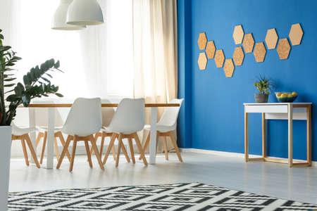 Acento de pared azul en la moderna sala de estar minimalista con área de comedor abierta, diseño escandinavo, ventana y decoración natural