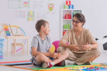 white wood floor: Smiling young boy and therapist sitting on floor and talking in school Stock Photo