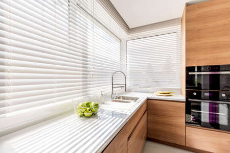 Modern bright kitchen interior with white horizontal window blinds, wooden cabinets with white countertop and household appliances Banco de Imagens - 84333551