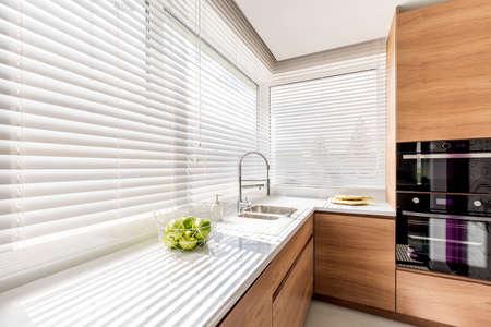 Moderner heller Kücheninnenraum mit weißen horizontalen Jalousien, hölzernen Kabinetten mit weißem Countertop und Haushaltsgeräten
