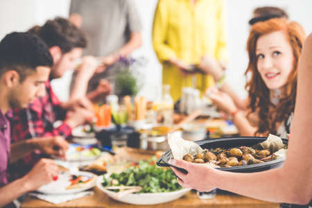 Vegetarian shares baked potatoes with vegan friends during vege meeting at home
