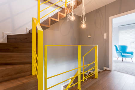 Wooden staircase with yellow railing in modern stylish entrance hallway with vintage bulb pendant light and white wall