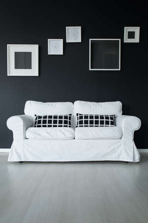 Stock Photo   White Comfortable Sofa On Panel Floor With Checkered Black  Pillows Against Black Wall With Frames