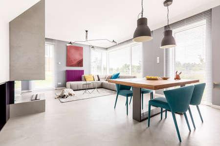 목조 공동 테이블, 베이지 색 소파 및 파란색 디자이너의 자와 함께 현대적인 디자인의 밝은 오픈 계획 아파트 인테리어