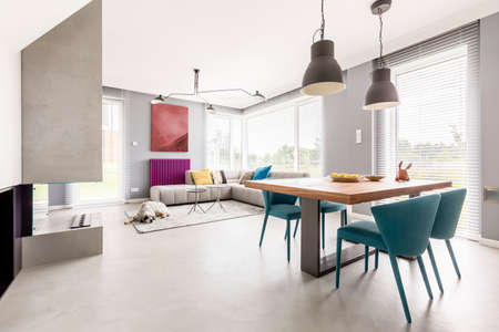 Bright open plan apartment interior in modern design with wooden communal table, beige couch and blue designer chairs