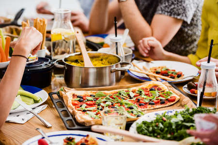 Communal table with fresh pizza millet groats healthy salad and hummus on veggie dinner Stok Fotoğraf
