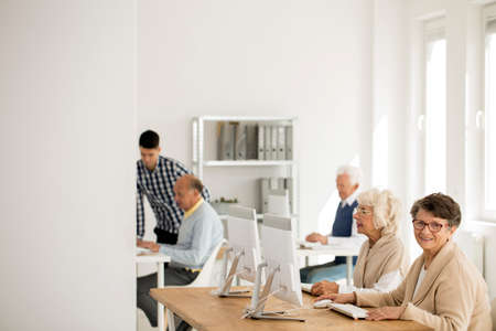 Older woman in glasses smiling and sitting at the desk with computer photo