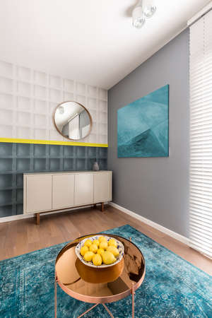 Black and white square molding with yellow detail on wall in modern colorful living room with sideboard, painting, copper coffee table and turquoise rug Stock Photo