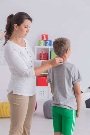 Young woman checking posture of boy in classroom with toys Stock Photo