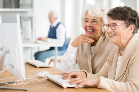 Twee oudere vrouwen met glazen die leren hoe te om computer samen te gebruiken