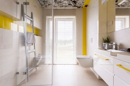 luxury room: Luxury stylish bathroom with white cabinets, mirror, ladder tower rack, window, glass door and yellow details