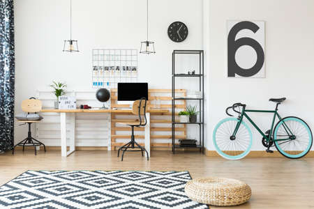 home office interior: Wicker pouf and dark green bicycle in freelancers open space apartment