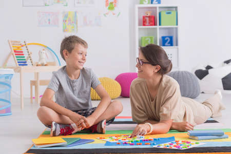 Smiling boy wearing sneakers sitting on floor talking to female therapist