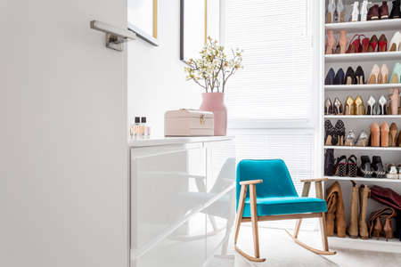 White cabinets in elegant classic walk-in closet with open storage for shoes, door, blue vintage armchair and pastel decor Фото со стока