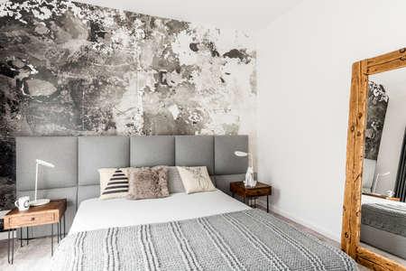 Grijs en wit interieur van moderne slaapkamer met houten nachtkastje, grote rustieke spiegel en abstracte grunge muur decor Stockfoto
