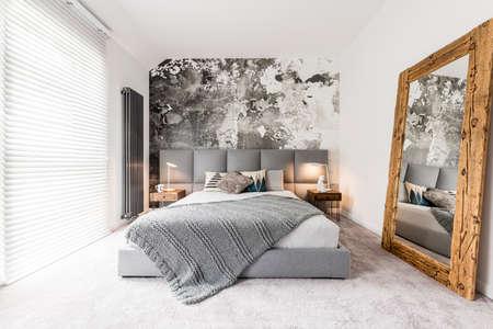 Kingsize bed met grijs vierkant hoofdeinde, grote rustieke houten spiegel en getextureerde muur in een trendy, minimalistisch appartement