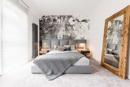 King-size bed with gray square headboard, large rustic wooden mirror and textured wall in trendy minimalist apartment