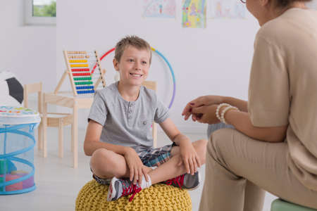 Smiling young boy sitting on yellow pouf in white classroom