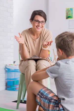 Smiling young woman wearing glasses talking to boy in white room Zdjęcie Seryjne
