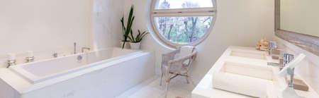 modern bathroom: Bright bathroom with sink, bathtub and oval window