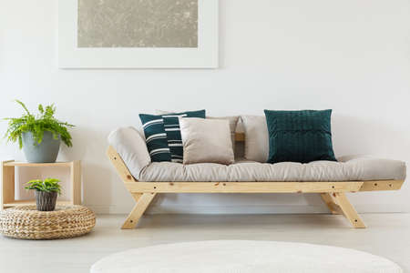 Trendy beige sofa with navy blue pillows and wooden frame, cupboard and plants in simple interior for a nature lover