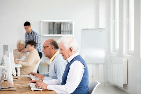 Two elder men using computers to test their knowledge of theory from lectures photo