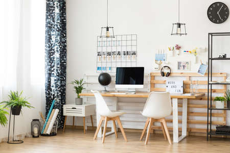 home office interior: Modern, minimalistic office with personal photos on the wall for a creative freelancer