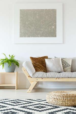 Acogedor interior en blanco estudio natural con sofá beige, madera, plantas, puf de ratán, obras de arte y alfombra estampada Foto de archivo - 83779650