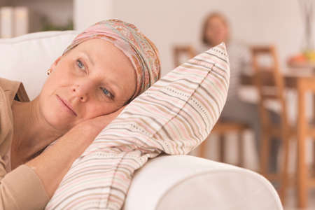 Tired woman after cancer treatment lying on couch at home Stock Photo