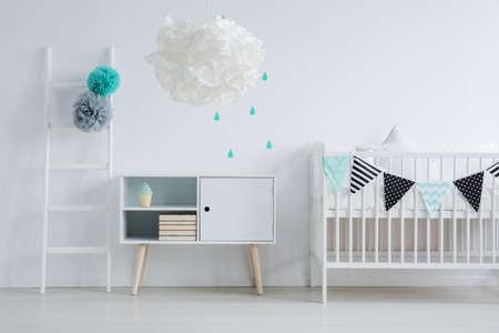 Moderne Lampe im Kinderzimmer zusammen mit einer kleinen Leiter, Minze-Wassertropfen-Aufklebern an der Wand und Washi Tape-Bett für ein Baby Standard-Bild - 84010452