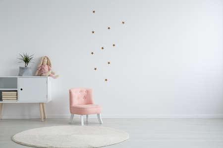 De stijlslaapkamer van Scandi met een installatie die zich op een witte kast naast een roze, elegante stoel, en een wit cirkeltapijt bevindt