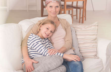 Sick mother after chemotherapy cancer treatment hugging small daughter