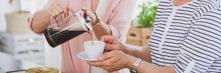 夫のカップにコーヒーを注いで、女のクローズ アップ 写真素材 - 84010830