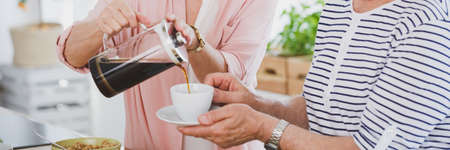 Close-up of woman pouring coffee into her husbands cup