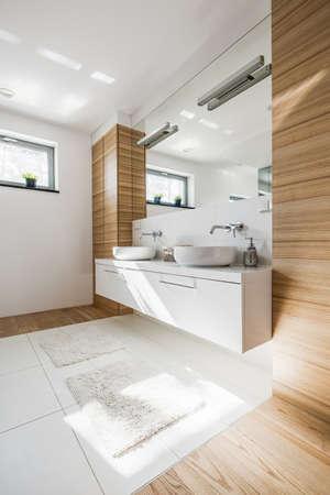 白い洗面化粧台トップと大きな鏡の美しいバスルームのインテリアのクロップ撮影 写真素材