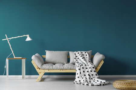 Teal geschilderde woonkamer met vlekkerige deken, moderne lamp en een kleine tafel