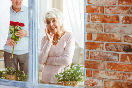 Old happy woman peeping through the window with small green plants Zdjęcie Seryjne